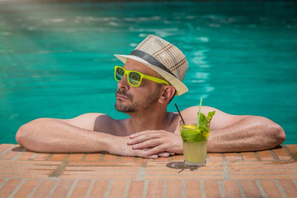 man in pool with cocktail