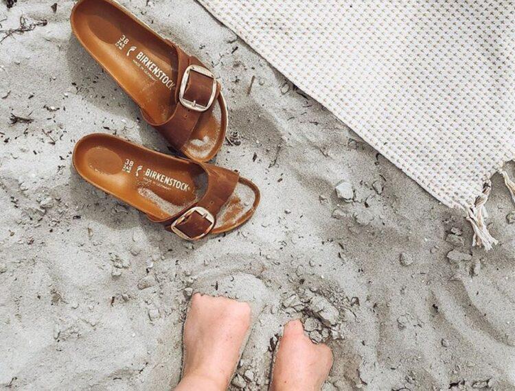 Birkenstock in sand next to feet in sand