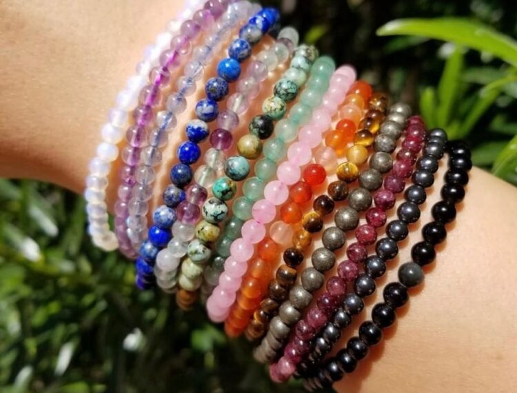 person wearing many different bracelets