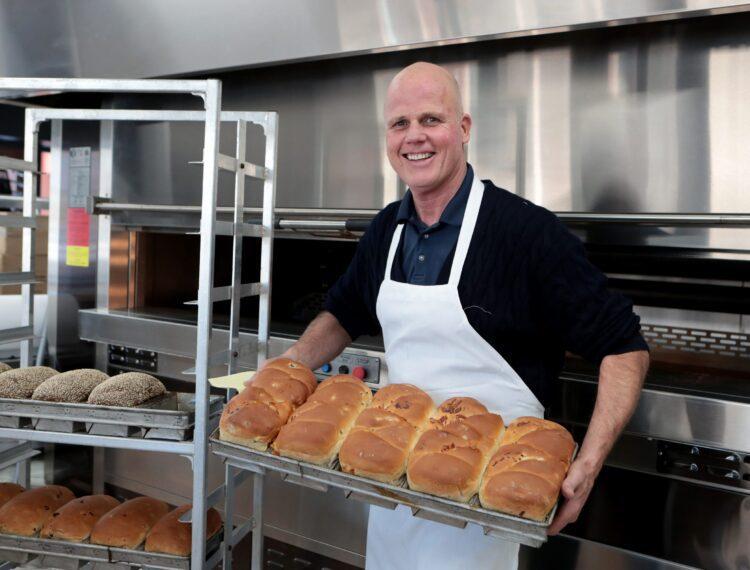 Man holding pan of bread