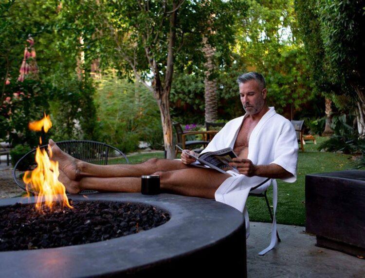 man sitting near fire pit