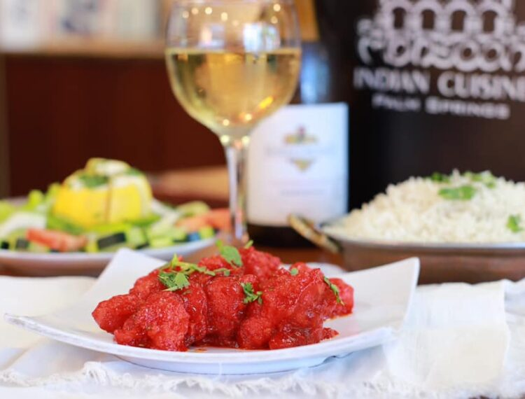 Indian food dish with glass of wine