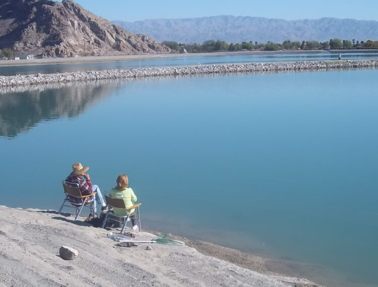 two people sitting by lake