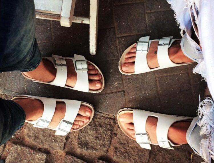 two people's feet wearing Birkenstocks