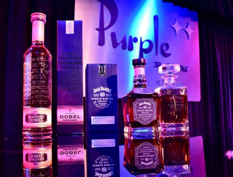 bottles of alcohol in front of Purple Room sign