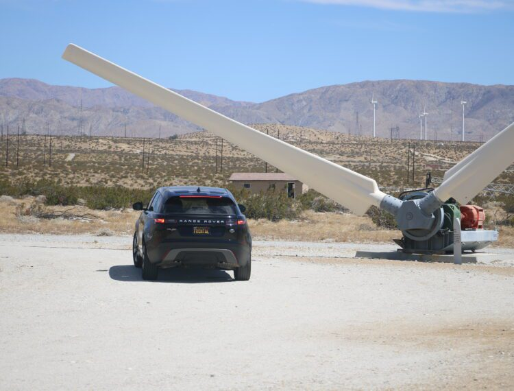 car parked near wind turbine blades