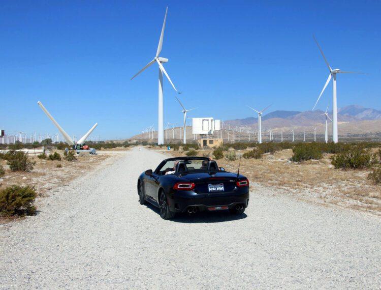 car driving near wind turbines