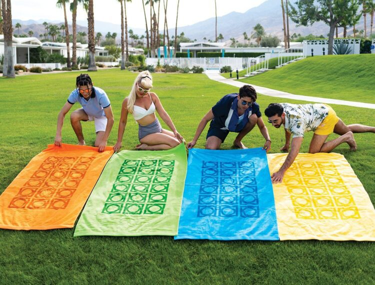 people on lawn laying out beach towels