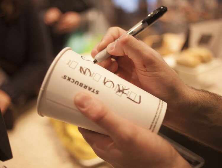 barista writing name on cup