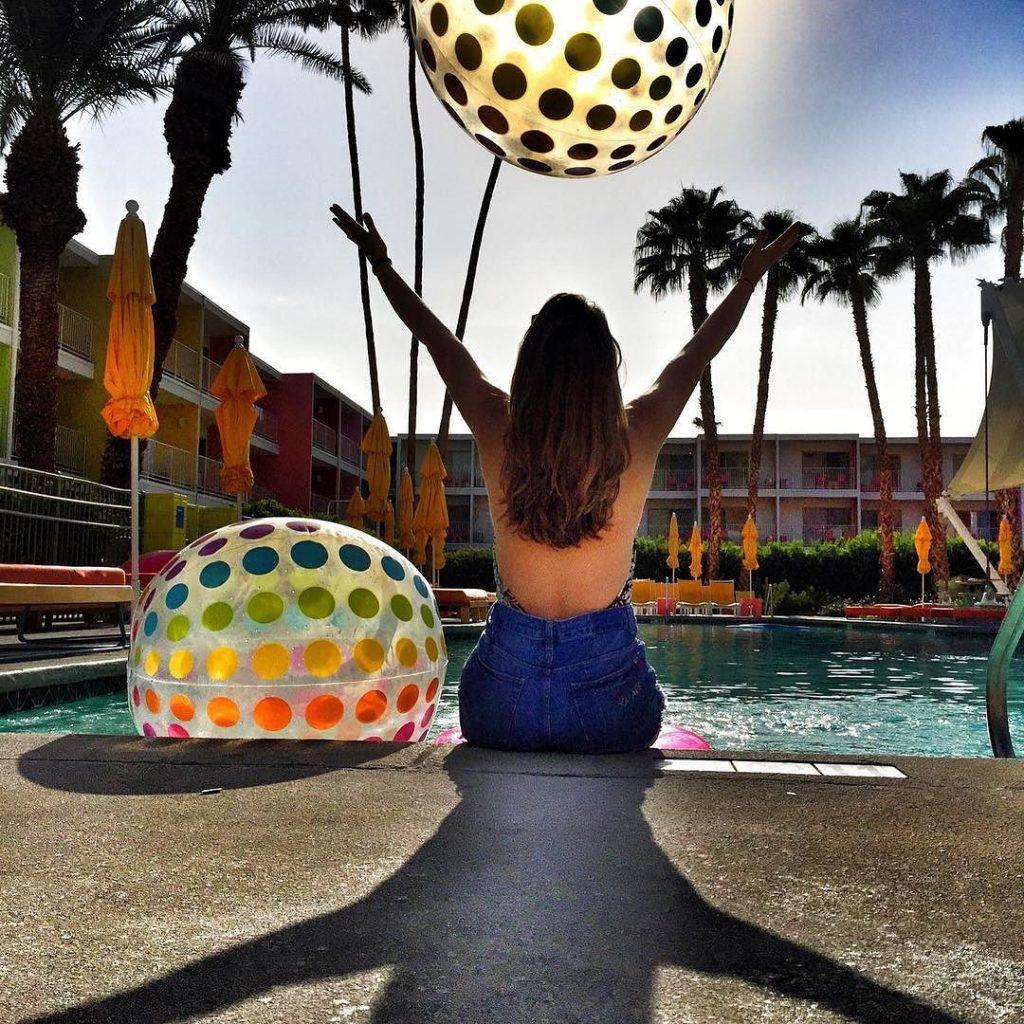 Woman sitting on edge of pool at Saguaro
