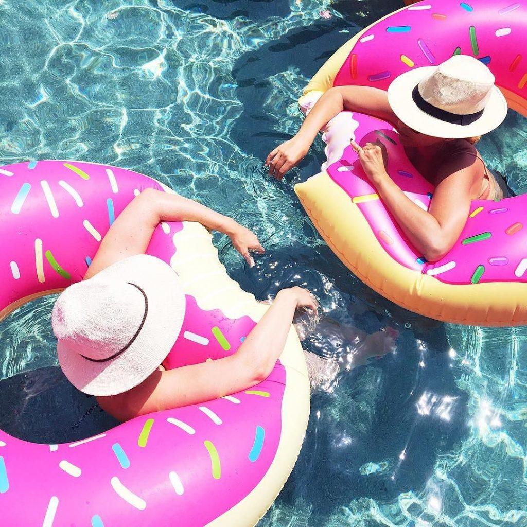 two people in inner tubes in pool