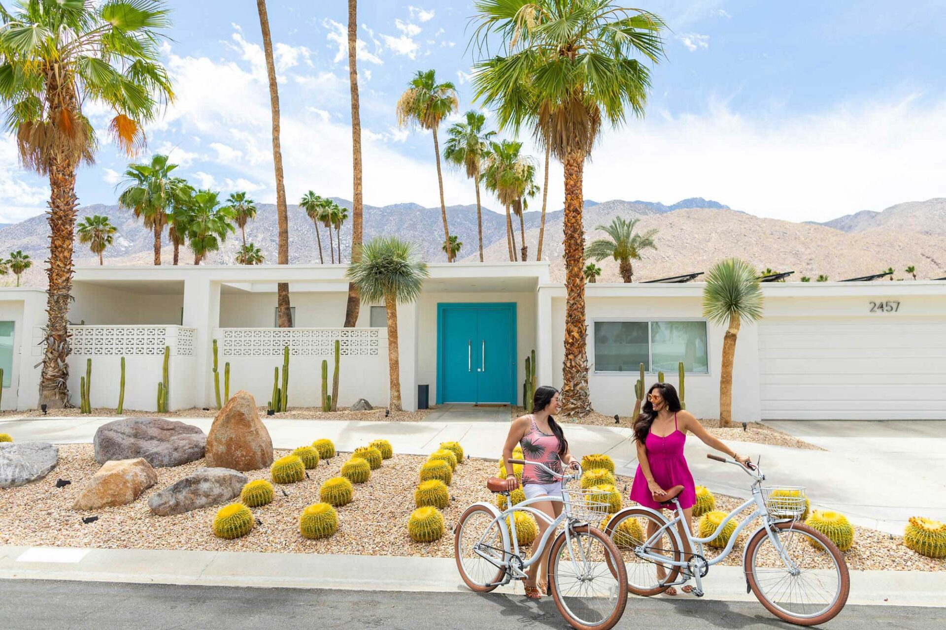 Two women on bikes in front of home